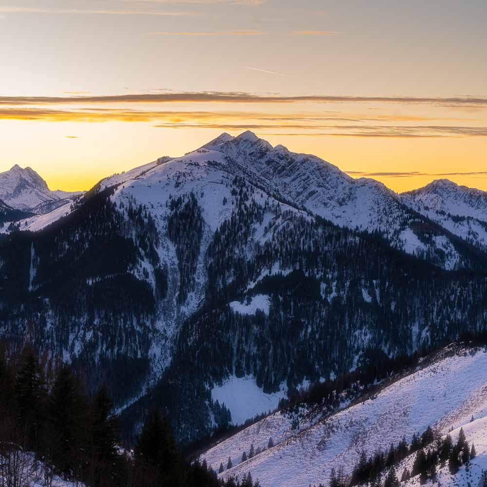 Winterlicher Berggipfel zum Sonnenuntergang